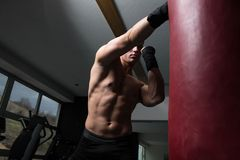 Shirtless Muscular Boxer With Punching Bag In Gym stock images