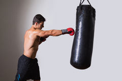 Shirtless muscular boxer with punching bag Stock Image