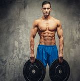 Muscular man in blue shorts holding weights in hands. Shirtless muscular guy holding weights. Some actions in studio stock photography