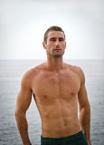 Shirtless muscular male model with sea behind Stock Photography