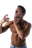 Shirtless muscular male model spraying cologne Stock Images