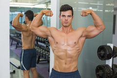 Shirtless muscular man flexing muscles in gym Royalty Free Stock Images