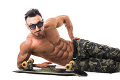 Shirtless muscular man on the floor with skateboard Royalty Free Stock Images