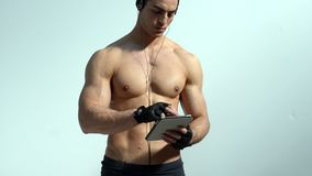 Shirtless muscular man holding tablet computer stock footage