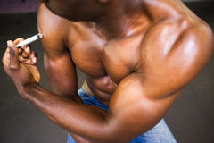 Shirtless muscular man injecting steroids. Close up of shirtless muscular man injecting steroids in the gym royalty free stock photos