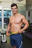 Shirtless muscular man measuring waist in gym Royalty Free Stock Photography