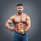 Shirtless muscular man pointing to fresh apple. Royalty Free Stock Photo