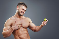 Shirtless muscular man pointing to lime. Royalty Free Stock Image