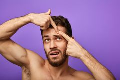 Shirtless muscular man is standing on blue background and squeezing pimples. royalty free stock photo
