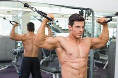 Shirtless muscular man using resistance band in gym Stock Photography