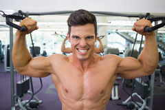 Shirtless muscular man using resistance band in gym Stock Images