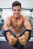 Shirtless muscular man using resistance band in gym Stock Photo
