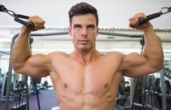 Shirtless muscular man using resistance band in gym Stock Image