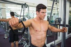 Shirtless muscular man using resistance band in gym Royalty Free Stock Photos