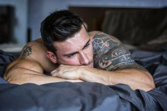 Shirtless male model lying alone on his bed. Shirtless muscular male model lying alone on bed in his bedroom, looking away with a seductive attitude royalty free stock images