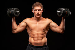 Shirtless muscular sportsman with serious face and dumbbells in his hands Royalty Free Stock Photography