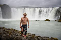 Shirtless and muscular boy walks around the Godafoss waterfall in Iceland
