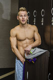 Shirtless muscular young male athlete in gym bathroom. Shirtless muscular young male athlete caught semi naked in gym changing room, embarassed Stock Photo