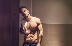 Shirtless young male athlete in gym dressing room with towel. Shirtless muscular young male athlete in gym dressing room changing, with towel on shoulder stock photography