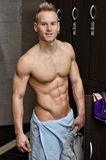 Shirtless muscular young male athlete in gym dressing room Stock Images