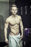 Shirtless muscular young male athlete in gym dressing room. Smiling with towel around waist Stock Images