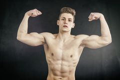 Shirtless muscular young man doing double biceps Royalty Free Stock Photos