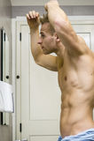 Shirtless, muscular young man looking at his hair Royalty Free Stock Image