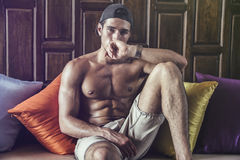 Shirtless muscular young man on sofa Royalty Free Stock Photography