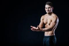 Shirtless muskulös idrotts- manpunkt med två händer som förbigår copyspace Sexig kroppsbyggare som visar hans kropp på svart Arkivfoton