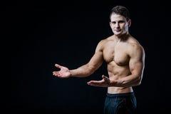 Shirtless muskulös idrotts- manpunkt med två händer som förbigår copyspace Sexig kroppsbyggare som visar hans kropp på svart Arkivbilder