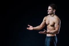 Shirtless muskulös idrotts- manpunkt med två händer som förbigår copyspace Sexig kroppsbyggare som visar hans kropp på svart Royaltyfri Fotografi
