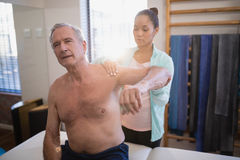 Shirtless senior male patient with arms raised receiving neck massage from female therapist Stock Photos