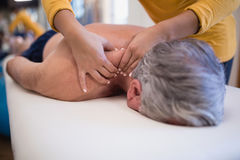 Shirtless senior male patient lying on bed receiving neck massage from female therapist. At hospital ward stock photography