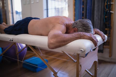 Shirtless senior male patient lying on white bed Stock Image