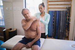 Shirtless senior male patient sitting on bed receiving neck massage from female therapist. At hospital ward Royalty Free Stock Photography