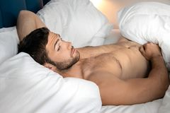 Shirtless hunky man with beard lies naked in bed. Handsome man with abs, muscular, hunky body and beard lies naked in between white sheets on bed royalty free stock photo