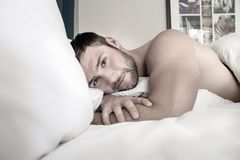 Shirtless hunky man with beard lies naked in bed. Handsome man with abs, muscular, hunky body and beard lies naked in between white sheets on bed stock photography