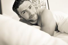 Shirtless hunky man with beard lies naked in bed stock photos