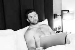 Shirtless hunky man with beard uses ipad tablet in bed stock photo