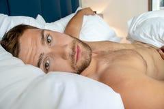 Shirtless sexy hunky mens met baard ligt naakt in bed stock afbeelding