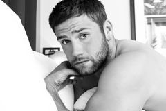 Shirtless sexy hunky mens met baard ligt naakt in bed royalty-vrije stock foto