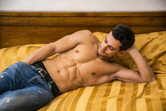 Shirtless sexy male model lying alone on his bed. In his bedroom, looking away with a seductive attitude Stock Photos