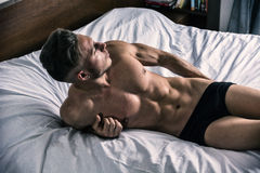 Shirtless sexy male model lying alone on his bed Stock Photography