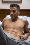 Shirtless sexy male model lying alone on his bed Stock Images