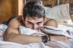 Shirtless sexy male model lying alone on his bed. In his bedroom, looking at camera with a seductive attitude Royalty Free Stock Image