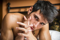 Shirtless sexy male model lying alone on his bed Royalty Free Stock Images