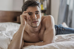 Shirtless sexy male model lying alone on his bed. In his bedroom, looking at camera with a seductive attitude Royalty Free Stock Photo