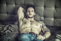 Shirtless sexy male model lying alone on his bed Stock Photo