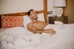 Shirtless male model lying alone on his bed in his bedroom.Carefree guy enjoying new day. stock images