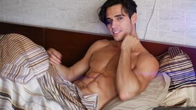 Shirtless male model lying alone on his bed